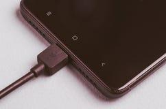 Smartphone preto com o carregador conectado/smartphone preto com o carregador conectado toned Vista superior fotografia de stock royalty free