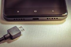 Smartphone preto e o carregador/smartphone preto e o carregador toned imagem de stock royalty free