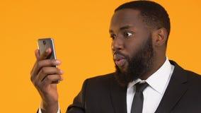 Smartphone preto entusiasmado da terra arrendada do homem de negócio, índice de observação do mercado financeiro vídeos de arquivo