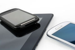 Smartphone preto na tabuleta preta com móbil branco além disso Foto de Stock