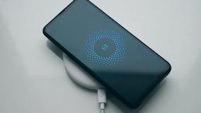 Smartphone preto recarregado em uma estação de carregamento sem fio Conceito da tecnologia sem fios video estoque