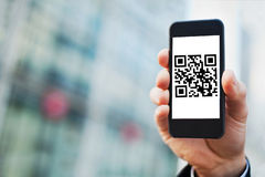Smartphone with QR code. Hand holding smartphone with QR code on the screen Stock Photography