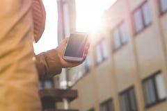 Smartphone que camina y que lleva de la mujer joven en sol Ciérrese para arriba de la muchacha que sostiene el teléfono móvil dis Imagen de archivo