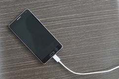 Smartphone que carrega na tabela de madeira Imagens de Stock