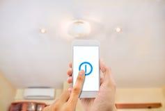 Smartphone que controla una luz imagenes de archivo