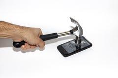 Smartphone que está sendo batido com um martelo, tela quebrada Fotos de Stock