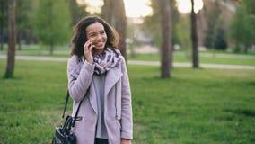 Smartphone que habla de la muchacha atractiva de la raza mixta y café de consumición en parque de la ciudad con los bolsos Mujer  Foto de archivo