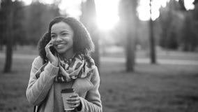 Smartphone que habla de la muchacha atractiva de la raza mixta y café de consumición en parque de la ciudad con los bolsos Mujer  Fotografía de archivo