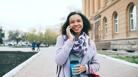 Smartphone que habla de la muchacha atractiva de la raza mixta y paseos de consumición del café en calle de la ciudad con los bol Foto de archivo libre de regalías