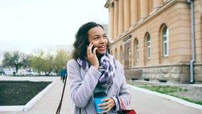 Smartphone que habla de la muchacha atractiva de la raza mixta y paseos de consumición del café en calle de la ciudad con los bol Imagen de archivo