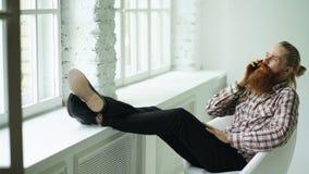 Smartphone que habla del hombre de negocios joven barbudo del inconformista mientras que se sienta en silla del offce con sus pie Imagen de archivo