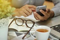 Smartphone que mecanografía del hombre en oficina del escritorio con la taza de café, los vidrios y el pequeño árbol imagenes de archivo