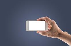 Smartphone que se sostiene derecho masculino con la pantalla en blanco foto de archivo libre de regalías