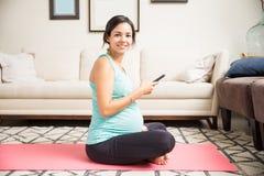 Smartphone que se sostiene femenino expectante sonriente en la estera del ejercicio imagenes de archivo