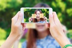 Smartphone que toma el desayuno adolescente de la consumición Foto de archivo libre de regalías