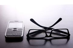 Smartphone with qwerty keypad and pair of eyeglasses. Photo of a smartphone or cellphone with a qwerty keypad and pair of eyeglasses Stock Images