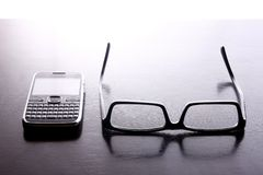 Smartphone with qwerty keypad and pair of eyeglasses. Photo of a smartphone or cellphone with a qwerty keypad and pair of eyeglasses Royalty Free Stock Photos