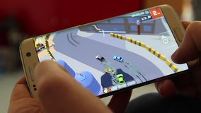 Smartphone racing game. Paris, France, January 17, 2018: man playing skidstorm cheetah games racing video game on his modern smartphone Samsung Galaxy S7 Edge At stock video footage