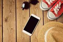 Smartphone raillent vers le haut du calibre avec des espadrilles et des lunettes de soleil de hippie Vue de ci-avant Image libre de droits