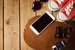 Smartphone raillent vers le haut du calibre avec les espadrilles et le sac de hippie Configuration plate Photographie stock libre de droits