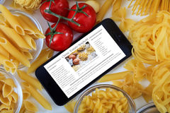 Smartphone with recipe on a table with pasta and vegetables. Smartphone with recipe on a white table with pasta and vegetables Stock Photo