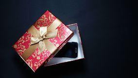Smartphone In Red Gift Box On Black Background. Smartphone In Red Gift Box On Black Background Royalty Free Stock Image