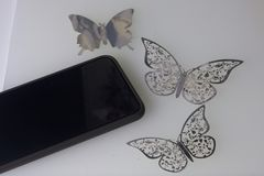 The smartphone rests on a white surface. Around him ornaments of butterflies, carved from foil. Stock Photos