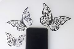 The smartphone rests on a white surface. Around him ornaments of butterflies, cut from foil. Stock Images