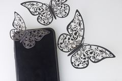 The smartphone rests on a white surface. Around him ornaments of butterflies, cut from foil. The smartphone rests on a white surface. Around him ornaments of Royalty Free Stock Photo