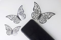 The smartphone rests on a white surface. Around him ornaments of butterflies, cut from foil. Stock Image