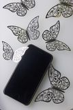 The smartphone rests on a white surface. Around him ornaments of butterflies, cut from foil. Royalty Free Stock Photo