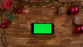 Smartphone is on the table, next to the New Year`s lights. Top view. Smartphone rests on a wooden table, next to the New Year`s lights and different toys. Top stock video footage