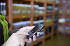 Smartphone in retail. A store manager uses BlackBerry smartphone to check inventory and transfer data wirelessly Stock Images