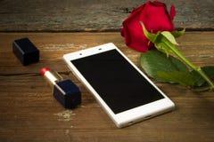 Smartphone, rose de rouge et rouge à lèvres sur une vieille table en bois Image libre de droits