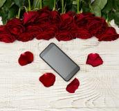 Smartphone, roses rouges et pétales sur un fond en bois clair, vue supérieure Photographie stock libre de droits