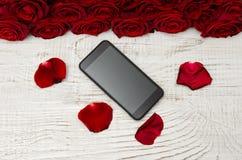 Smartphone, roses rouges et pétales sur un fond en bois clair, vue supérieure Images libres de droits