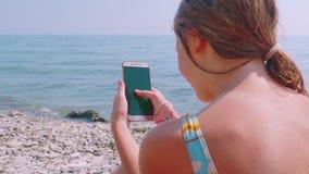 Smartphone running da mulher caucasiano loura nova contra o mar filme