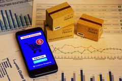 Smartphone runs an online shopping app with cardboard boxes. con. Cept about this type of financial charts include stacks of bar compare between the expansion of Stock Photography
