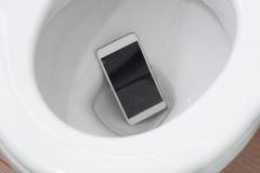 Smartphone s'est laissé tomber dans la toilette photo libre de droits