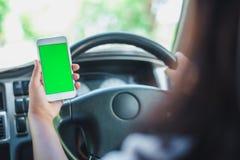 Smartphone s?tter p? radion i en bil gr?n plats arkivbild