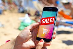 Smartphone sale advertising. Girl on the beach holding a smartphone a sale advertising on the screen. Marketing, discount, internet, cell phone publicity royalty free stock image
