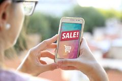 Smartphone sale advertising. Internet publicity. Girl holding a smartphone a sale advertising on the screen. Marketing, discount, internet, cell phone publicity royalty free stock photo