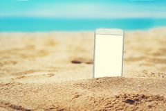 Smartphone in the sand on a beach in the summer. Smartphone in the sand on a beach with blank white screen for Infographic Global Business Marketing investment stock image
