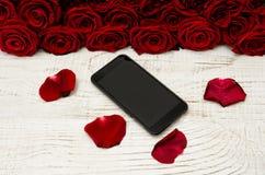 Smartphone se repose sur une table en bois blanche sur le fond des pétales et un bouquet des roses Image stock