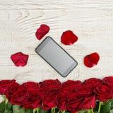 Smartphone se trouve sur une table en bois blanche entourée par des pétales et un bouquet des roses Image libre de droits