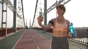 Smartphone self-portrait of senior female runner. Stunning fit woman in her 40s standing on city bridge at sunrise with water bottle and making self-portrait on stock footage