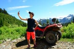 Smartphone Selfie από τον έφηβο παραγωγής Υ με ATV & x28 Για όλα τα εδάφη Vehicle& x29  Σταθμευμένος στην ορεινή δασική φύση στοκ φωτογραφία