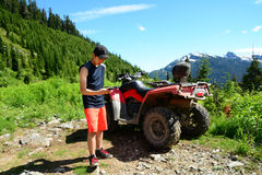 Smartphone Selfie by Generation Y Teenager with ATV (All Terrain Vehicle) Parked in Mountainous Forest Valley. Male Generation Y Teenager uses iPhone6 to snap a Stock Photography