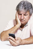 Smartphone and senior man at home Stock Photography