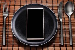 Smartphone served on a black plate with cutlery on the side. Concept of social media addiction royalty free stock photos